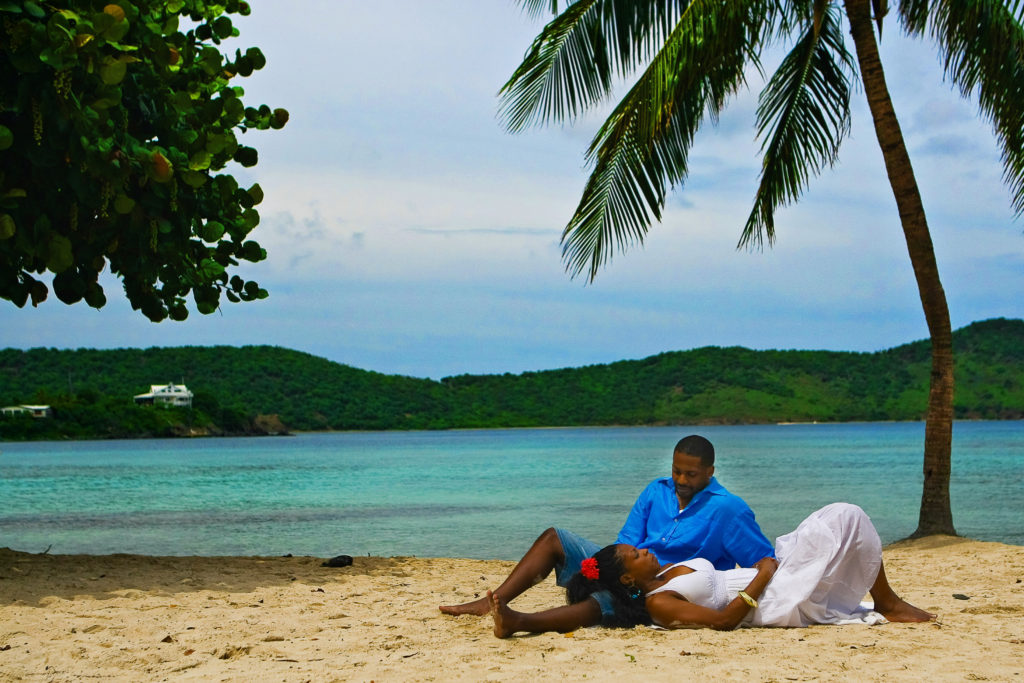 St.Thomas USVI Engagement laying on the beach under the palm tree at Magens Bay Beach.